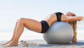 Κατάλληλος ξανθός τεντώνοντας την πίσω στη σφαίρα άσκησης στην παραλία Στοκ Φωτογραφίες
