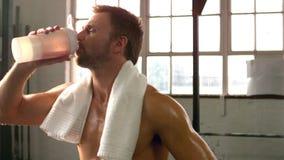 Κατάλληλο άτομο που πίνει το πρωτεϊνικό κούνημα στη γυμναστική φιλμ μικρού μήκους