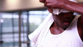 Κατάλληλο άτομο που σκουπίζει το brow του και που χαμογελά στη κάμερα απόθεμα βίντεο