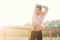 Κατάλληλο άτομο που τεντώνει το βραχίονα και τον ώμο του που θερμαίνουν στο καθαρό αέρα Στοκ Εικόνες