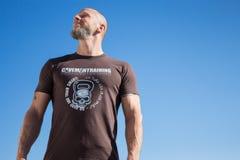 Κατάλληλο άτομο στο καφετί πουκάμισο Kettlebell στοκ εικόνες με δικαίωμα ελεύθερης χρήσης