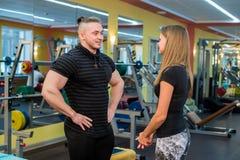Κατάλληλο ελκυστικό νέο ζεύγος σε μια γυμναστική που εξετάζει ένα ταμπλέτα-PC δεδομένου ότι παρακολουθούν την πρόοδο και την ικαν Στοκ Φωτογραφίες