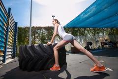 Κατάλληλο κορίτσι με τη γιγαντιαία ρόδα στροφής φορτηγών workout Στοκ Εικόνες