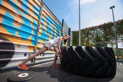 Κατάλληλο κορίτσι με τη γιγαντιαία ρόδα στροφής φορτηγών workout Στοκ Εικόνα