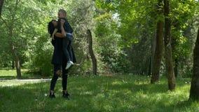 Κατάλληλο παιχνίδι γυναικών με το παιδί της που αγκαλιάζει και που αγκαλιάζει και που ανυψώνει τον στην παιδική χαρά φιλμ μικρού μήκους
