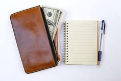Κατάλογος αγορών, κενά σημειωματάριο και μετρητά στο καφετί πορτοφόλι Στοκ Φωτογραφία