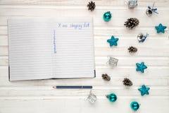 Κατάλογος αγορών Χριστουγέννων σχετικά με το άσπρο ξύλινο υπόβαθρο Deco διακοπών Στοκ εικόνα με δικαίωμα ελεύθερης χρήσης