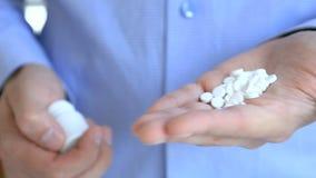 Κατά πρόκληση της αυτοκτονίας, αρσενικά τη χέρια τινάζουν έξω όλα τα χάπια από το φιαλίδιο Ένα άτομο κρατά μια χούφτα των χαπιών απόθεμα βίντεο