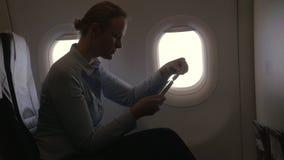 Κατά την άποψη αεροπλάνων της γυναίκας που κάνει την πληρωμή με την τραπεζική κάρτα που χρησιμοποιούν το smartphone και dongle γι απόθεμα βίντεο