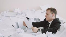 Κατά τη διάρκεια της εργασίας, ο εργαζόμενος γραφείων αντιμετωπίζει τις δυσκολίες Ένας νεαρός άνδρας σε ένα κοστούμι γραφείων είν φιλμ μικρού μήκους