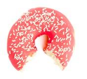 Κατά το ήμισυφαγωμένο ?αγωμένο κόκκινο doughnut με τη ζάχαρη ψεκάζει Στοκ Φωτογραφίες