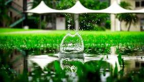 Καταβρέχοντας νερό στο πράσινο υπόβαθρο στοκ φωτογραφία
