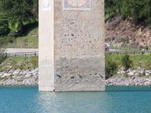 Καταδυμένος πύργος της εκκλησίας reschensee, άτομο που κολυμπά δίπλα σε το στοκ φωτογραφία