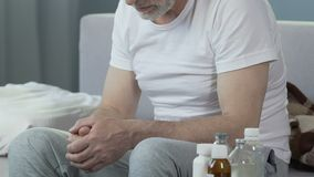 Καταθλιπτική ανώτερη αρσενική συνεδρίαση στο κρεβάτι, μπουκάλια με τα φάρμακα που στέκονται εδώ κοντά φιλμ μικρού μήκους