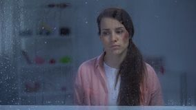 Καταθλιπτική γυναίκα με την πληγωμένη συνεδρίαση προσώπου πίσω από το βροχερό παράθυρο, επίθεση φιλμ μικρού μήκους