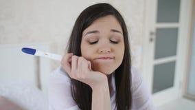 Καταθλιπτική γυναίκα με τη δοκιμή εγκυμοσύνης στο δωμάτιο φιλμ μικρού μήκους
