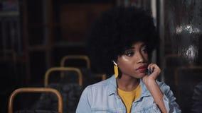 Καταθλιπτική, λυπημένη γυναίκα αφροαμερικάνων younf που οδηγά δημόσιες συγκοινωνίες τη νύχτα Αυτή που φαίνεται έξω το παράθυρο απόθεμα βίντεο