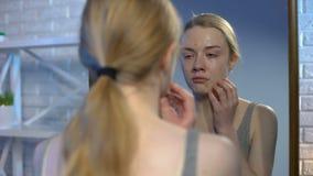 Καταθλιπτική νέα γυναίκα που εξετάζει τα σπυράκια εφηβείας στο πρόσωπο στην αντανάκλαση καθρεφτών απόθεμα βίντεο