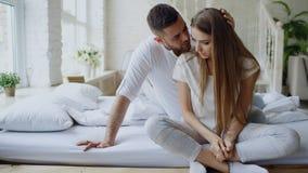 Καταθλιπτική νέα συνεδρίαση γυναικών στο κρεβάτι και να φωνάξει ενώ το boylfriend της έρχεται και αγκαλιάζει το της και το φιλί σ στοκ εικόνα