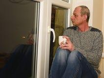 Καταθλιπτική συνεδρίαση ατόμων Μεσαίωνα κοντά στο παράθυρο Λυπημένος καφές κατανάλωσης ατόμων Στοκ Φωτογραφία