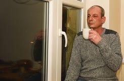 Καταθλιπτική συνεδρίαση ατόμων Μεσαίωνα κοντά στο παράθυρο Λυπημένος καφές κατανάλωσης ατόμων Στοκ φωτογραφία με δικαίωμα ελεύθερης χρήσης
