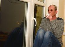 Καταθλιπτική συνεδρίαση ατόμων Μεσαίωνα κοντά στο παράθυρο Λυπημένος καφές κατανάλωσης ατόμων Στοκ εικόνα με δικαίωμα ελεύθερης χρήσης