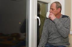 Καταθλιπτική συνεδρίαση ατόμων Μεσαίωνα κοντά στο παράθυρο Λυπημένος καφές κατανάλωσης ατόμων Στοκ φωτογραφίες με δικαίωμα ελεύθερης χρήσης