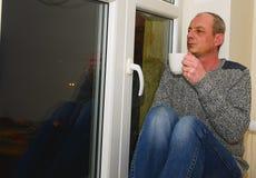 Καταθλιπτική συνεδρίαση ατόμων Μεσαίωνα κοντά στο παράθυρο Λυπημένος καφές κατανάλωσης ατόμων Στοκ Εικόνα