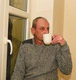 Καταθλιπτική συνεδρίαση ατόμων Μεσαίωνα κοντά στο παράθυρο Λυπημένος καφές κατανάλωσης ατόμων Στοκ Εικόνες