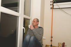 Καταθλιπτική συνεδρίαση ατόμων Μεσαίωνα κοντά στο παράθυρο Λυπημένος καφές κατανάλωσης ατόμων στρέψτε μαλακό Στοκ φωτογραφία με δικαίωμα ελεύθερης χρήσης