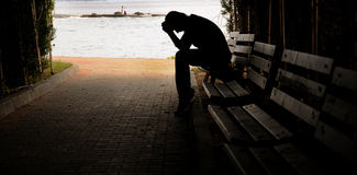 Καταθλιπτική συνεδρίαση νεαρών άνδρων στον πάγκο Στοκ Φωτογραφία