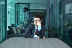 Καταθλιπτικός επιχειρηματίας που κάθεται μόνο στην αρχή Στοκ εικόνα με δικαίωμα ελεύθερης χρήσης