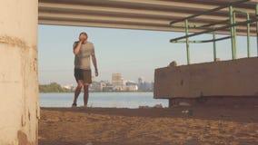 Καταθλιπτικός νεαρός άνδρας κάτω από τη γέφυρα, στα πλαίσια της πόλης βραδιού απόθεμα βίντεο