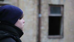 Καταθλιπτικός νεαρός άνδρας που εξετάζει την απόσταση κοντά στο παλαιό σπίτι τούβλου, διανοητικό κενό απόθεμα βίντεο
