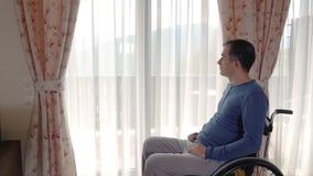 Καταθλιπτικός νεαρός άνδρας στην αναπηρική καρέκλα κοντά στο παράθυρο στο σπίτι απόθεμα βίντεο