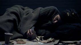 Καταθλιπτικός πρόσφυγας που βρίσκεται στο πάτωμα που εξετάζει τους οικογενειακούς αριθμούς εγγράφου, μνήμες στοκ εικόνες