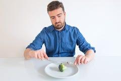 Καταθλιπτικό άτομο που κάνει δίαιτα και που τρώει μόνο τα λαχανικά στοκ φωτογραφία με δικαίωμα ελεύθερης χρήσης
