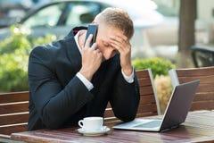 Καταθλιπτικός επιχειρηματίας που μιλά στο κινητό τηλέφωνο Στοκ Εικόνες