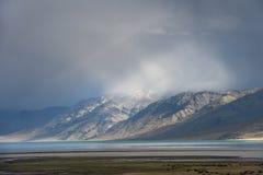 Καταιγίδα στη λίμνη βουνών: τα σύννεφα κατεβαίνουν στην επιφάνεια του μπλε νερού, μέσω των σύννεφων που μια ακτίνα του φωτός του  Στοκ Φωτογραφίες