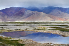 Καταιγίδα στα υψηλά βουνά της Tso Kara λίμνης: τα ιώδη σύννεφα κατεβαίνουν στα βουνά, η ήρεμη επιφάνεια της λίμνης refle Στοκ Εικόνες