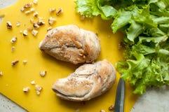Κατακόκκινα στήθη κοτόπουλου με τη σαλάτα φύλλων και το συντριμμένο ξύλο καρυδιάς στον κίτρινο τέμνοντα πίνακα Στοκ Εικόνες