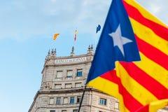 Καταλανική σημαία που κυματίζει μπροστά από την τράπεζα του κτηρίου της Ισπανίας στο κέντρο πόλεων της Βαρκελώνης κατά τη διάρκει στοκ εικόνες
