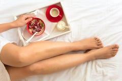 κατανάλωση έννοιας υγιής Χέρια γυναικών ` s που κρατούν το κύπελλο με το muesli και τα παγωμένα μούρα Στοκ εικόνες με δικαίωμα ελεύθερης χρήσης