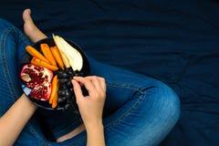 κατανάλωση έννοιας υγιής Χέρια γυναικών ` s που κρατούν το πιάτο με τα αχλάδια, τα σταφύλια, persimmon και ροδιών τα φρούτα Στοκ εικόνες με δικαίωμα ελεύθερης χρήσης