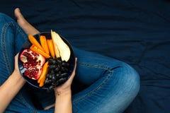 κατανάλωση έννοιας υγιής Χέρια γυναικών ` s που κρατούν το πιάτο με τα αχλάδια, τα σταφύλια, persimmon και ροδιών τα φρούτα Στοκ Φωτογραφίες