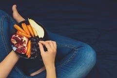 κατανάλωση έννοιας υγιής Χέρια γυναικών ` s που κρατούν το πιάτο με τα αχλάδια, τα σταφύλια, persimmon και ροδιών τα φρούτα Στοκ Φωτογραφία