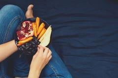 κατανάλωση έννοιας υγιής Χέρια γυναικών ` s που κρατούν το πιάτο με τα αχλάδια, τα σταφύλια, persimmon και το ρόδι Στοκ εικόνα με δικαίωμα ελεύθερης χρήσης