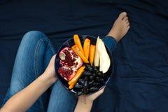 κατανάλωση έννοιας υγιής Χέρια γυναικών ` s που κρατούν το πιάτο με τα αχλάδια, τα σταφύλια, persimmon και ροδιών τα φρούτα Στοκ φωτογραφίες με δικαίωμα ελεύθερης χρήσης