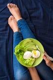κατανάλωση έννοιας υγιής Χέρια γυναικών ` s που κρατούν το πιάτο με το μαρούλι, τις φέτες αβοκάντο και τα λαθραία αυγά Στοκ Εικόνες