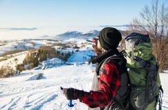 Κατανάλωση ατόμων από μια φιάλη ισχίων στο χιονώδες βουνό στοκ φωτογραφίες